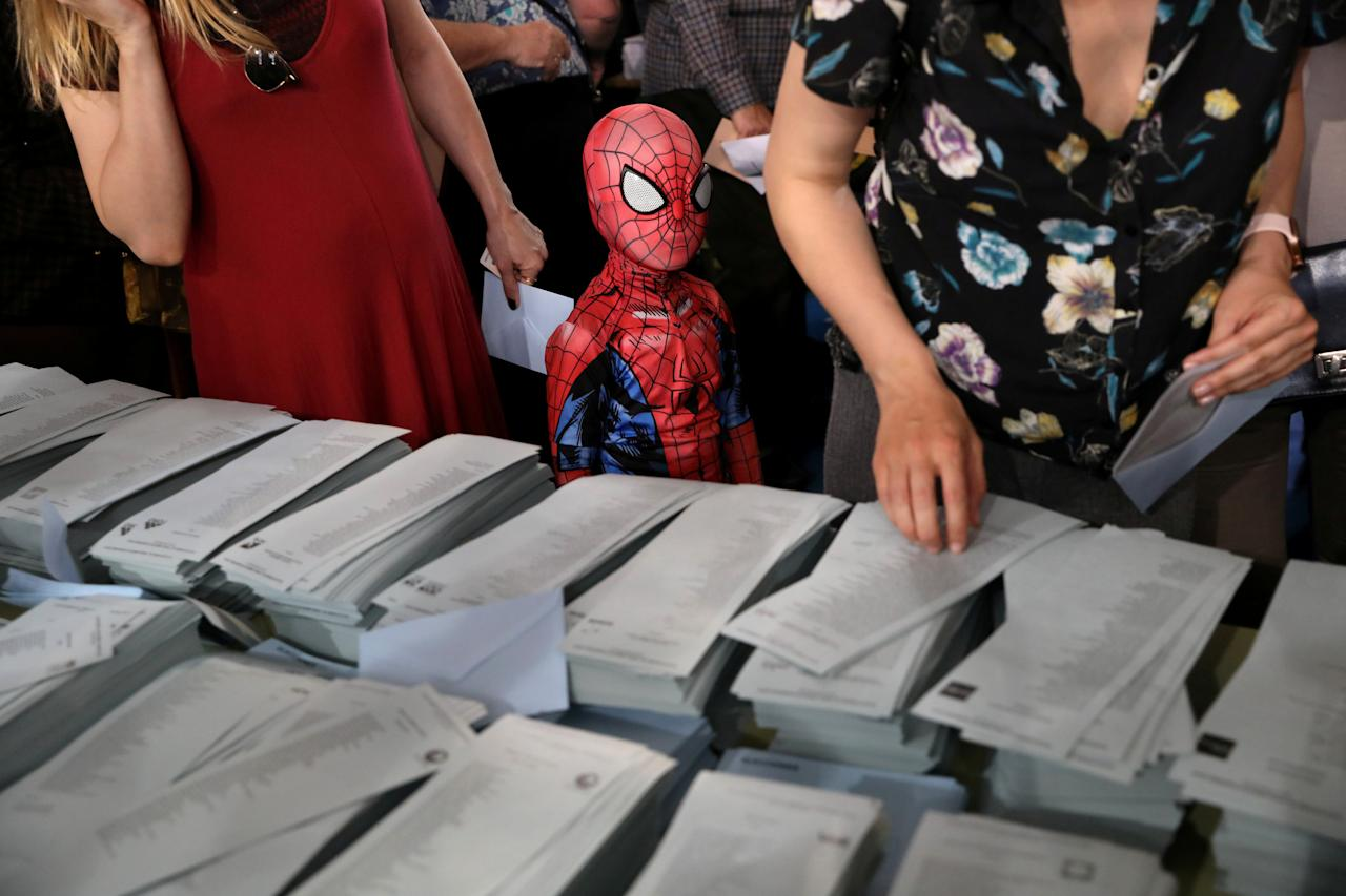 A kid in a Spiderman costume stands next to a ballot table for the European Parliament election at a polling station in Madrid, Spain, May 26, 2019. REUTERS/Susana Vera     TPX IMAGES OF THE DAY