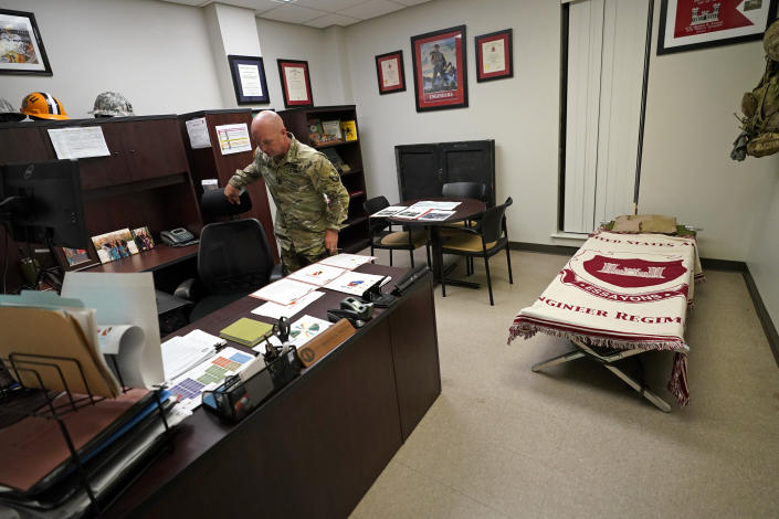 Capt. Michael Switzer goes to sit at his desk before he goes to sleep in his office at Camp Beauregard in Pineville, La., Friday, July 30, 2021. (AP Photo/Gerald Herbert)