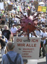 """Participants of a demonstration protest with signs on the Rhine meadows against the measures to combat the coronavirus in Duesseldorf, Germany, Sunday, Sept.20, 2020. Sign reads """"you and m , we all for truth , freedom, love, peace."""".(Roberto Pfeil/dpa via AP)"""