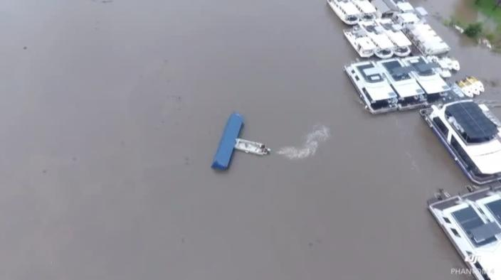 Boat pushes a container away from moving towards houseboats in Wisemans Ferry