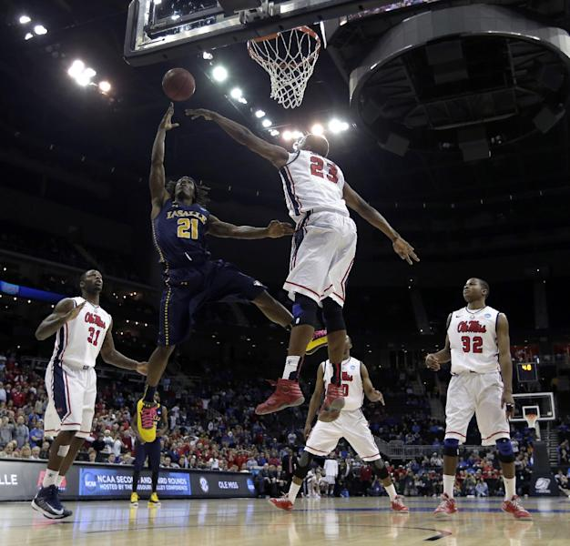 La Salle guard Tyrone Garland (21) gets past Mississippi forward Reginald Buckner (23) to make the game-winning shot in a third-round game of the NCAA college basketball tournament Sunday, March 24, 2013, in Kansas City, Mo. La Salle won the game 76-74. (AP Photo/Charlie Riedel)