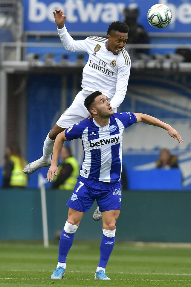 Real Madrid's Eder Militao left, duels for the ball with Alaves' Lucas Perez during the Spanish La Liga soccer match between Real Madrid and Alaves at Mendizorroza stadium, in Vitoria, northern Spain, Saturday, Nov. 30, 2019. (AP Photo/Alvaro Barrientos)