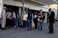 Militia officers stand guard at the entrance of a bakery as people line up to buy bread in Caracas, Venezuela March 17, 2017. REUTERS/Marco Bello