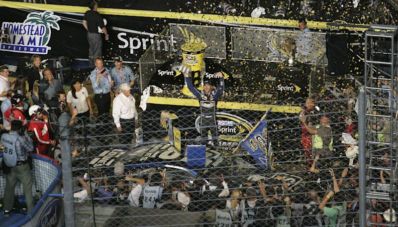 Jimmie Johnson, center, celebates after winning the NASCAR Sprint Cup Series Championship in Homestead, Fla., Sunday, Nov 17, 2013. (AP Photo/Jim Topper)