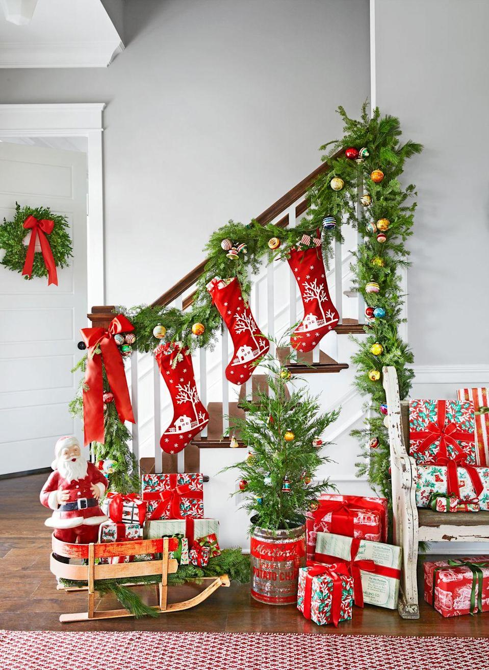 """<p>Stockings, colorful ornaments, and plenty of wrapped presents liven up the entryway of this <a href=""""https://www.countryliving.com/home-design/house-tours/g3856/christmas-tennessee-house-tour/"""" rel=""""nofollow noopener"""" target=""""_blank"""" data-ylk=""""slk:Tennessee home"""" class=""""link rapid-noclick-resp"""">Tennessee home</a>.</p><p><strong><a class=""""link rapid-noclick-resp"""" href=""""https://www.amazon.com/Yoland-Plating-Multicolor-Christmas-Ornaments/dp/B014IOKTEK?tag=syn-yahoo-20&ascsubtag=%5Bartid%7C10050.g.1247%5Bsrc%7Cyahoo-us"""" rel=""""nofollow noopener"""" target=""""_blank"""" data-ylk=""""slk:SHOP ORNAMENTS"""">SHOP ORNAMENTS</a></strong></p>"""