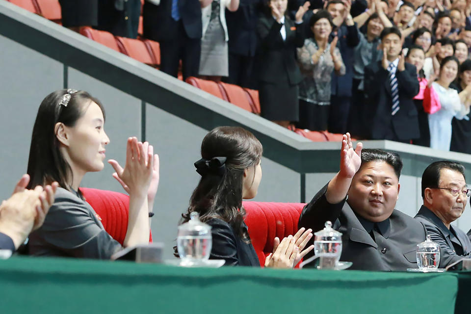 FILE - In this June 3, 2019, file photo provided by the North Korean government, North Korean leader Kim Jong Un, second right, waves with his wife Ri Sol Ju, center, during the grand gymnastics and artistic performance at the May Day Stadium in Pyongyang. The woman next to Ri Sol Ju appears to be Kim's sister, Kim Yo Jong, who state media said attended the performance. The coronavirus is the biggest reason for North Korea's decision not to come to Tokyo. The nation has shut its borders tighter than normal, worried that its fragile health care system and rickety economy could not withstand a major outbreak. That, in turn, could put the ruling Kim family in danger. (Korean Central News Agency/Korea News Service via AP, File)