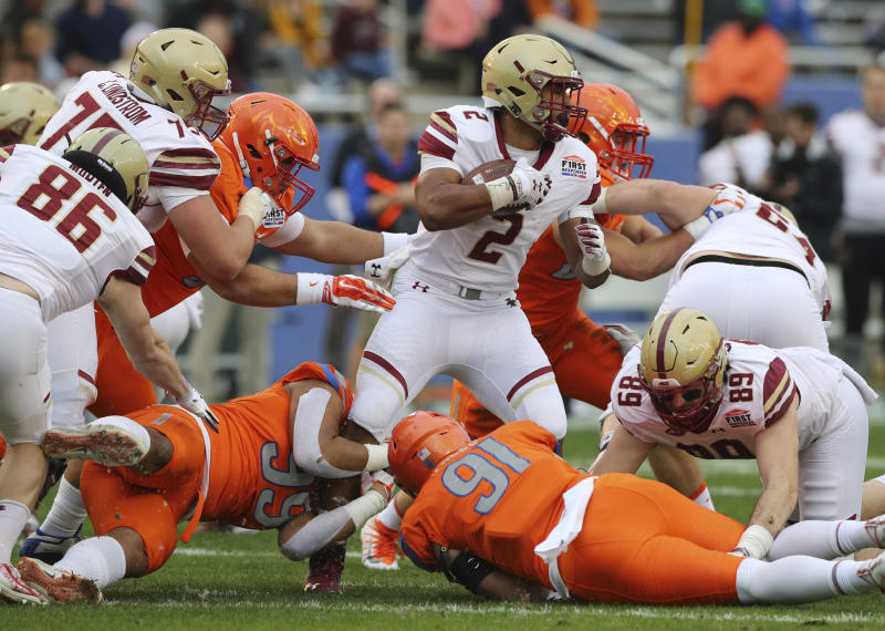 Boston College running back AJ Dillon (2) tries to break tackle by Boise State linebacker Curtis Weaver (99) and defensive end Durrant Miles (91) during the first half of the First Responder Bowl NCAA football game Wednesday, Dec. 26, 2018, in Dallas. (AP Photo/Richard W. Rodriguez)