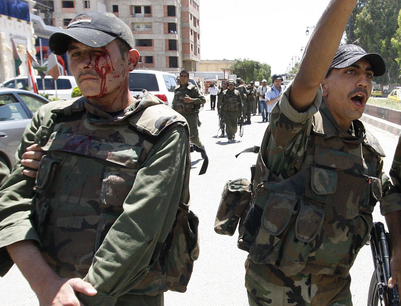 An injured Syrian army soldier, left, walks next to his comrade after a roadside bomb hit their military truck, in Daraa city, southern Syria, Wednesday, May 9, 2012. A roadside bomb struck a Syrian military truck Wednesday, wounding six soldiers just seconds after a convoy carrying the head of the U.N. observer mission passed by. An Associated Press reporter who was traveling in the U.N. convoy said the blast blew out the military truck's windows and caused a plume of black smoke. The U.N. convoy was not hit. (AP Photo/Muzaffar Salman)