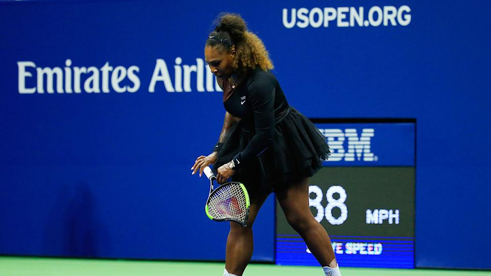 Serena Williams holds the racquet that is set to fetch a large sum at auction.