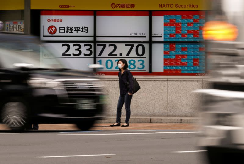 A passerby wearing a protective face mask stands in front of an electronic board showing Japan's Nikkei averageoutside a brokerage, amid the coronavirus disease (COVID-19) outbreak, in Tokyo