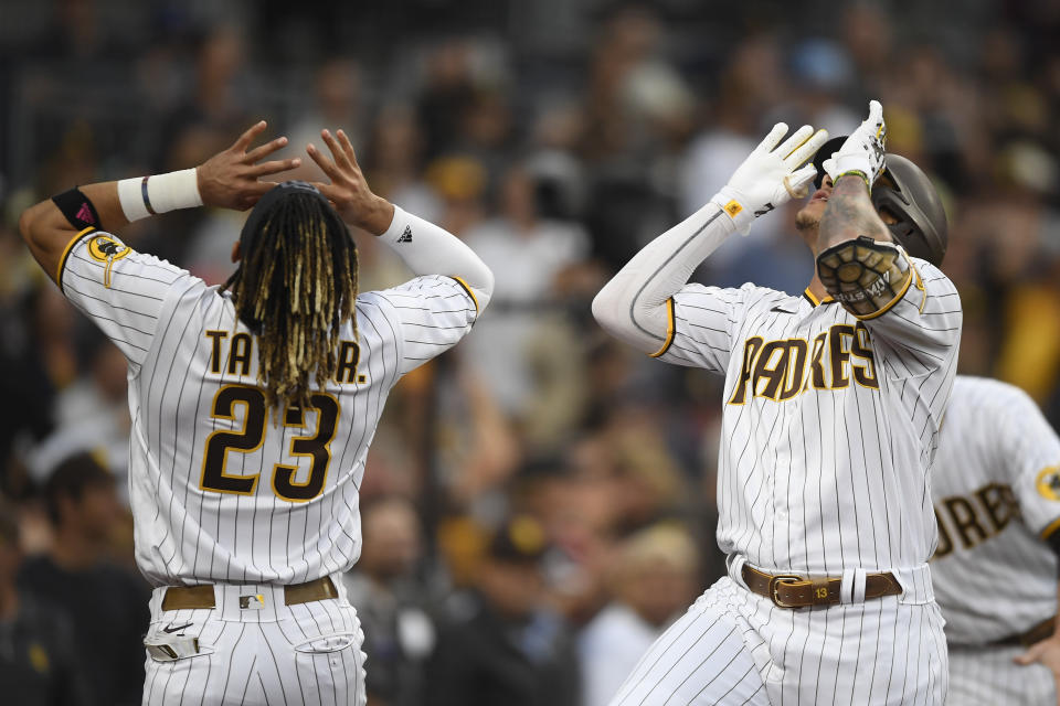 San Diego Padres' Manny Machado (13), right, celebrates with Fernando Tatis Jr. (23) after hitting a solo home run during the first inning of a baseball game against the Los Angeles Dodgers Wednesday, June 23, 2021, in San Diego. (AP Photo/Denis Poroy)