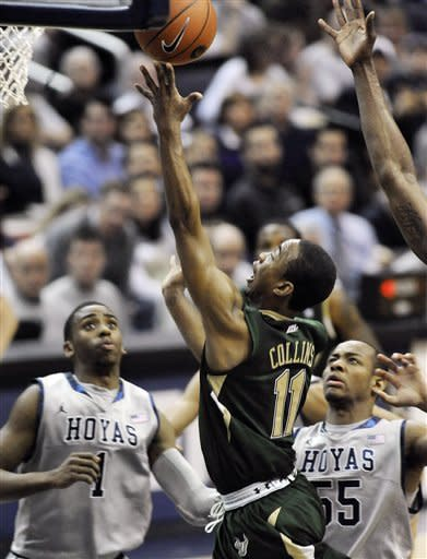 South Florida's Anthony Collins (11) drives to the basket and scores as Georgetown defenders, Hollis Thompson (1) and Jabril Trawick (55) look on during first half of an NCAA college basketball game, Saturday, Feb. 4, 2012, in Washington. Georgetown won 75-45. (AP Photo/Richard Lipski)