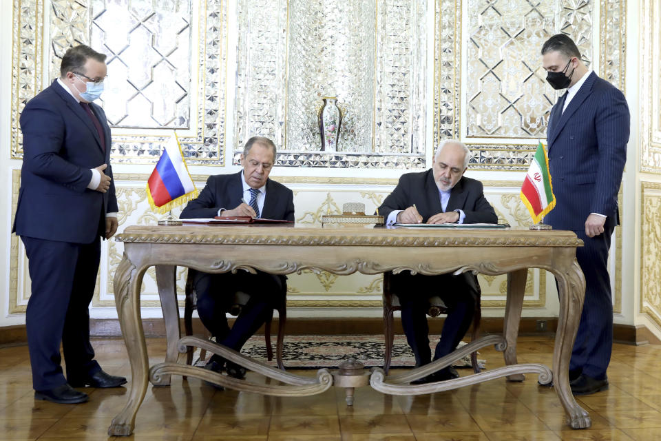 In this photo released by the Iranian Foreign Ministry, Iranian Foreign Minister Mohammad Javad Zarif, center right, and his Russian counterpart Sergey Lavrov, center left, sign agreements after their talks in Tehran, Iran, Tuesday, April 13, 2021. Iran's foreign minister warned Tuesday that an attack on its main nuclear enrichment site at Natanz affects ongoing negotiations in Vienna over its tattered atomic deal with world powers. (Iranian Foreign Ministry via AP)
