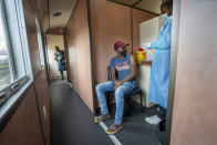 A person receives a COVID-19 vaccine on a train at the Swartkops railroad yard outside Gqeberha, South Africa, Thursday Sept. 23, 2021. South Africa has sent a train carrying COVID-19 vaccines into one of its poorest provinces to get doses to areas where healthcare facilities are stretched. The vaccine train, named Transvaco, will go on a three-month tour through the Eastern Cape province and stop at seven stations for two weeks at a time to vaccinate people. (AP Photo/Jerome Delay)