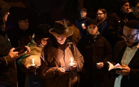 People hold candles outside the Tree of Life Synagogue after a shooting there left 11 people dead in the Squirrel Hill neighbourhood of Pittsburgh - Credit: AFP