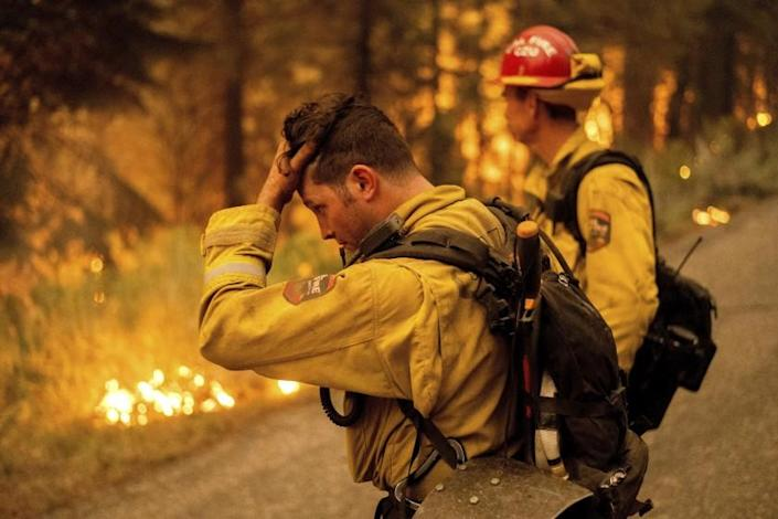 Firefighter Jesse Forbes rubs his head while battling the Dixie Fire near Prattville in Plumas County, Calif., on Friday, July 23, 2021. (AP Photo/Noah Berger)