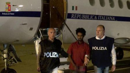 Medhanie Yehdego Mered is pictured with Italian policemen as they land at Palermo airport, Italy, following his arrest in Khartoum, Sudan