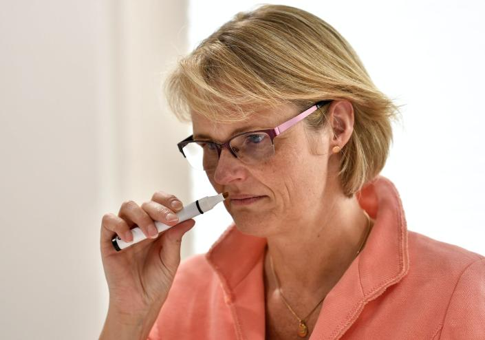 A woman smelling a dry erase marker