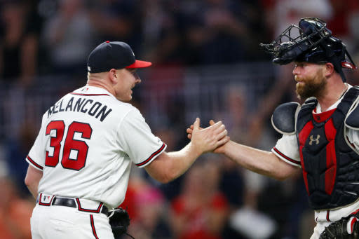 Atlanta Braves relief pitcher Mark Melancon (36) and catcher Brian McCann (16) celebrate after the Braves defeated the New York Mets 5-3 in a baseball game Tuesday, Aug. 13, 2019, in Atlanta. Melancon earned the save. (AP Photo/John Bazemore)