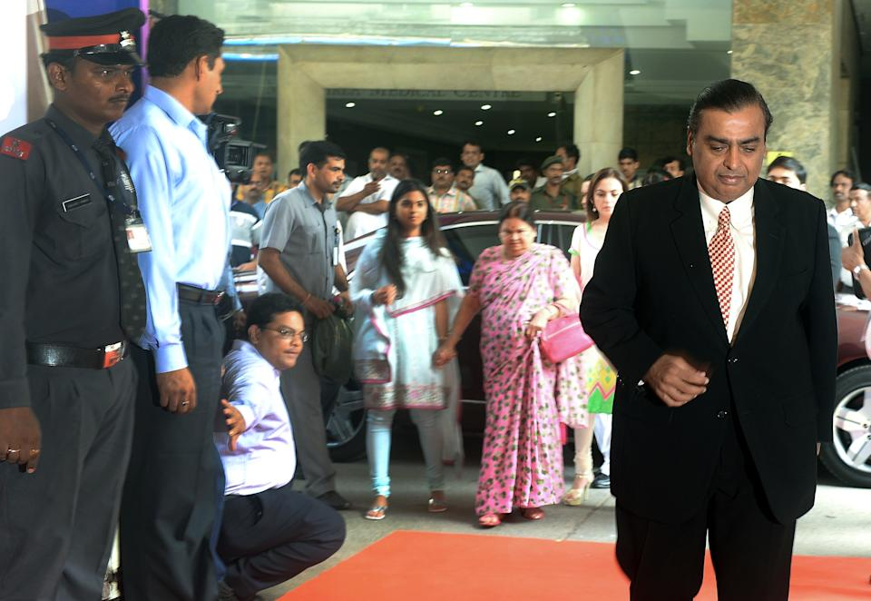 Reliance Industries Chairman Mukesh Ambani (R) arrives followed by his wife Nita (2R) mother Kokilaben (3R) and daughter Isha (4R) for the company's annual general meeting in Mumbai on June 6, 2013. India's largest private firm Reliance Industries plans to invest 1.5 trillion rupees (USD26 billion) in all its businesses over the next three years, its chairman Mukesh Ambani told shareholders. Reliance is India's largest private oil and gas explorer with a strong presence in the petrochemicals and polyester sectors and has expanded into the fast-growing broadband and retail segments in recent years. AFP PHOTO/Indranil MUKHERJEE