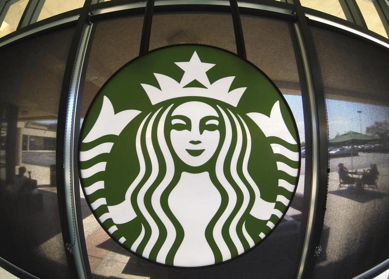 The Starbucks logo hangs on a window inside a newly designed Starbucks coffee shop in Fountain Valley, Californi