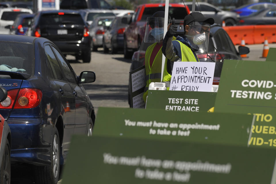 Workers direct cars as they wait in line for coronavirus testing at Dodger Stadium Tuesday, July 14, 2020, in Los Angeles. (AP Photo/Mark J. Terrill)