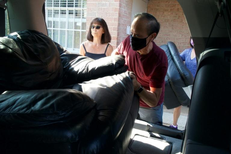 Levan Kuck (L) and Mike Wong (R), volunteers with Homes Not Borders, a nonprofit helping refugees, asylum seekers and Special Immigrant Visa holders settle in the United States, load furniture into a vehicle in Landover, Maryland (AFP/Bastien INZAURRALDE)