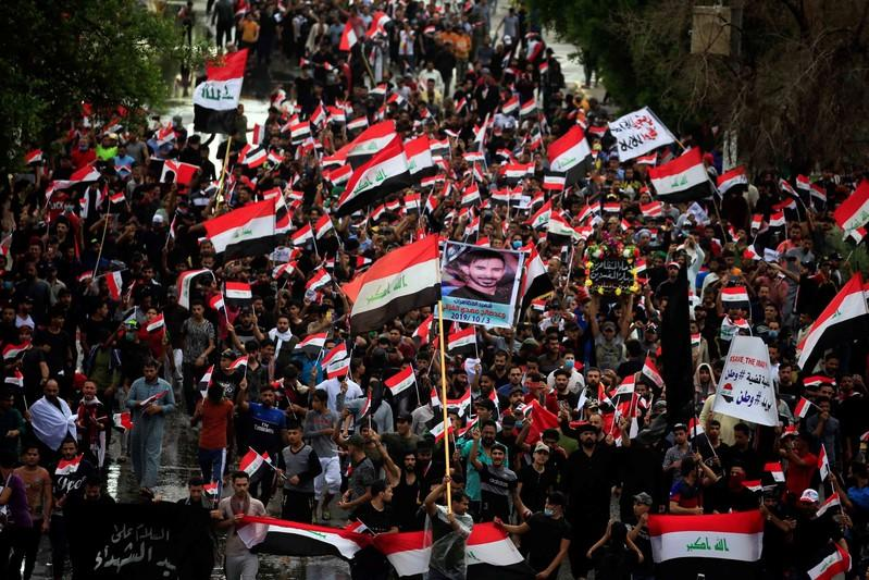 Demonstrators hold the Iraqi flag as they gather during a protest in Najaf