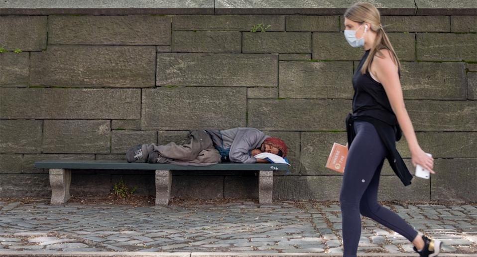 Pictured is a homeless man laying on a park bench while a woman wearing a mask passes him.