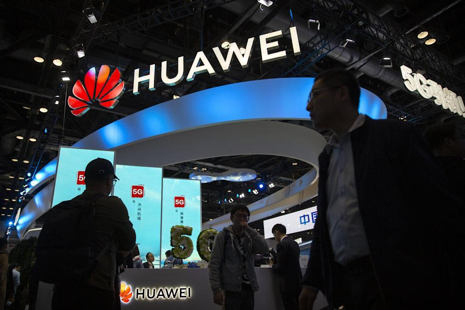 Attendees walk past a display for 5G services from Huawei at the PT Expo in Beijing, China, on October 31, 2019. Photo: AP Photo