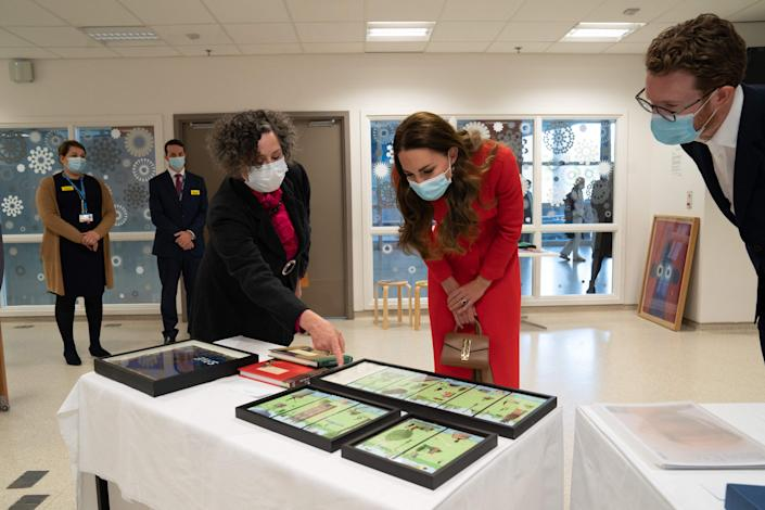 Britain's Catherine, Duchess of Cambridge (C) is shown artwork on display by Catsou Roberts (L), director of Arts and Health, Vital Arts, during a visit to Royal London Hospital Whitechapel in east London, on May 7, 2021, to meet staff and hear how the hospital uses art to benefit patients and staff. (Photo by Arthur EDWARDS / various sources / AFP) (Photo by ARTHUR EDWARDS/AFP via Getty Images)