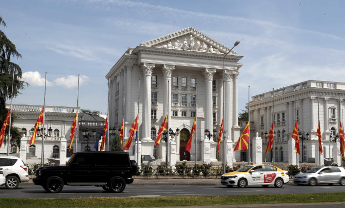 National flags lowered at half mast in honor of the victims in the burned out field hospital in western town of Tetovo, are pictured in front of the Government building in Skopje, North Macedonia, on Saturday, Sept. 11, 2021. Hundreds of people have marched Saturday in northwestern town of Tetovo to honor their 14 countrymen killed in a deadly fire that broke earlier this week and destroyed COVID-19 field hospital. (AP Photo/Boris Grdanoski)