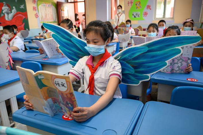 Elementary school students wear wings May 20 to maintain social distancing amid concerns over the spread of COVID-19 in a classroom in Taiyuan in China's northern Shanxi province.
