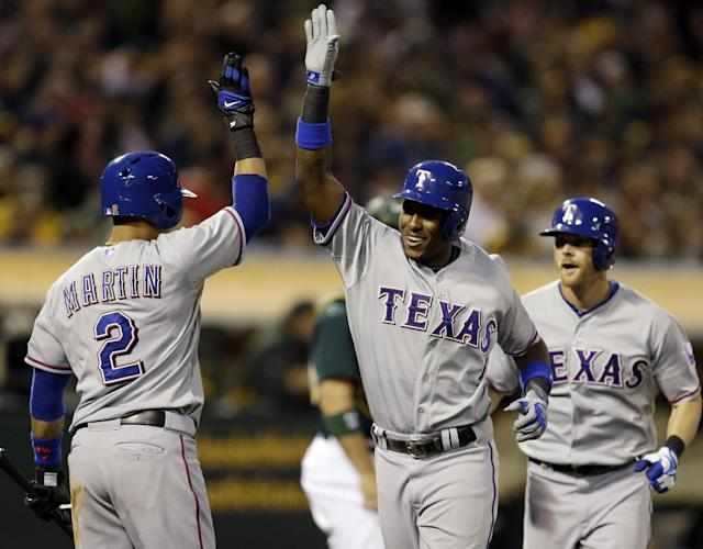 Texas Rangers' Jurickson Profar, center, is congratulated by Leonys Martin (2) and Craig Gentry, right, after Profar hit a two run home run off Oakland Athletics' Tommy Milone in the fourth inning of a baseball game, Friday, Aug. 2, 2013, in Oakland, Calif. (AP Photo/Ben Margot)