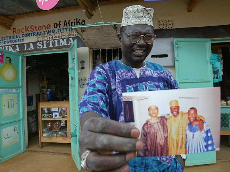 Malik Obama, the older brother of Barack, holds an undated picture outside his shop in Siaya in eastern Kenya: AP
