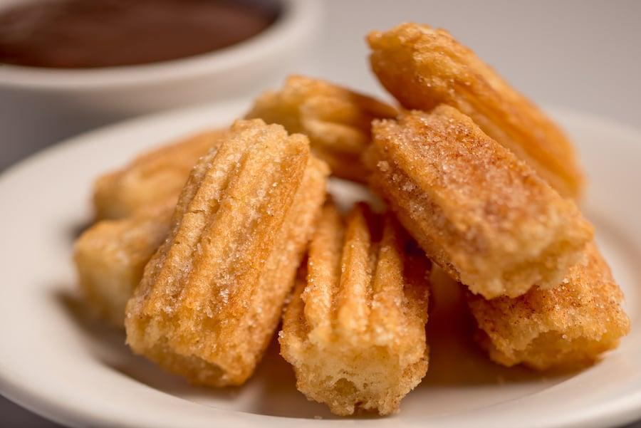 "<p>Churros are such a classic Disney treat. In fact, you can find them in some form at every Disney park! These churro bites are simple to make as long as you have a piping bag or zip top bag to squeeze the dough into the hot oil.</p> <p><strong>Get the recipe:</strong> <a href=""http://disneyparks.disney.go.com/blog/2020/04/cooking-up-the-magic-create-disneymagicmoments-at-home-with-disney-parks-churro-bites-recipe/"" class=""link rapid-noclick-resp"" rel=""nofollow noopener"" target=""_blank"" data-ylk=""slk:Disney's churro bites"">Disney's churro bites</a></p>"