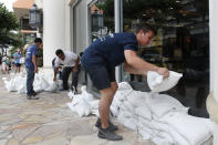 <p>Austin Seawright, right, stacks sandbags in front of a closed store in preparation for Hurricane Lane, Thursday, Aug. 23, 2018, in Honolulu. (Photo: John Locher/AP) </p>