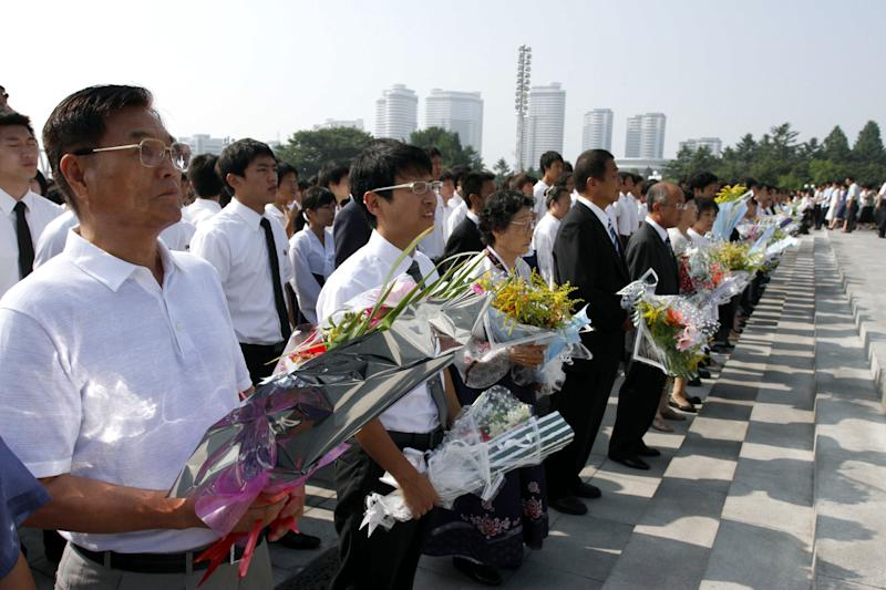 North Koreans lay flowers at the statues on Mansu Hill of the country's late leaders, Kim Il Sung and Kim Jong Il, to mark the 18th anniversary of Kim Il Sung's death on Sunday, July 8, 2012, in Pyongyang, North Korea. (AP Photo/Kim Kwang Hyon)