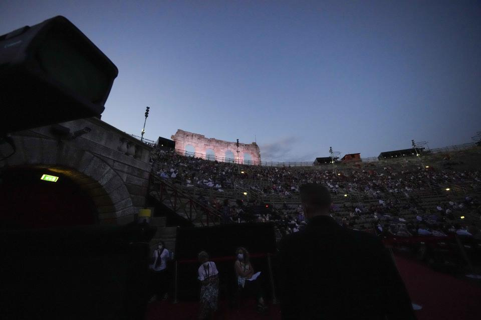 Spectators attend the 'Cavalleria Rusticana' lyric opera, at the Arena di Verona theatre, in Verona, Italy, Friday, June 25, 2021. The Verona Arena amphitheater returns to staging full operas for the first time since the pandemic struck but with one big difference. Gone are the monumental sets that project the scene to even nosebleed seats in the Roman-era amphitheater, replaced by huge LED screens with dynamic, 3D sets that are bringing new technological experiences to the opera world. (AP Photo/Luca Bruno)