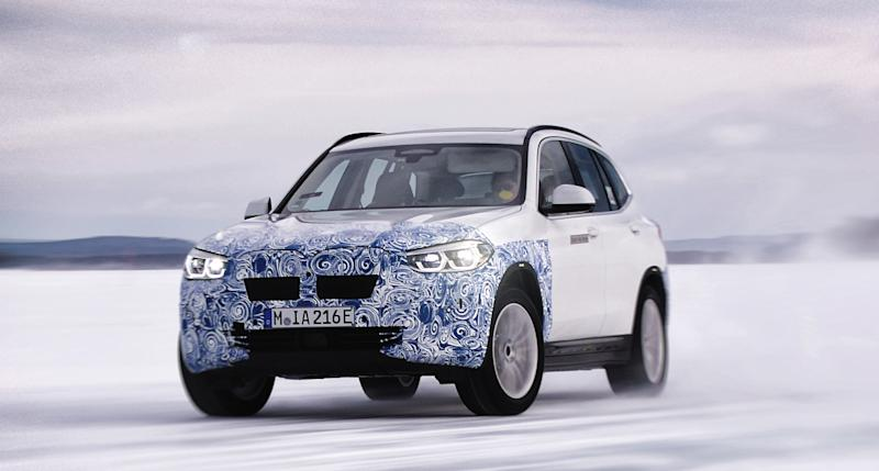A prototype BMW iX3, a compact electric luxury crossover SUV, shown undergoing winter testing.