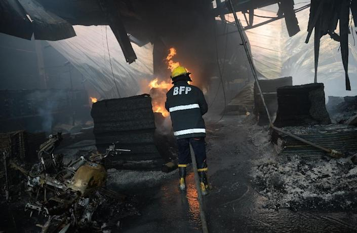 Philippine fire fighters try to put out a blaze at a footwear factory in the Valenzuela district on the edge of Manila on May 13, 2015 (AFP Photo/Ted Aljibe)
