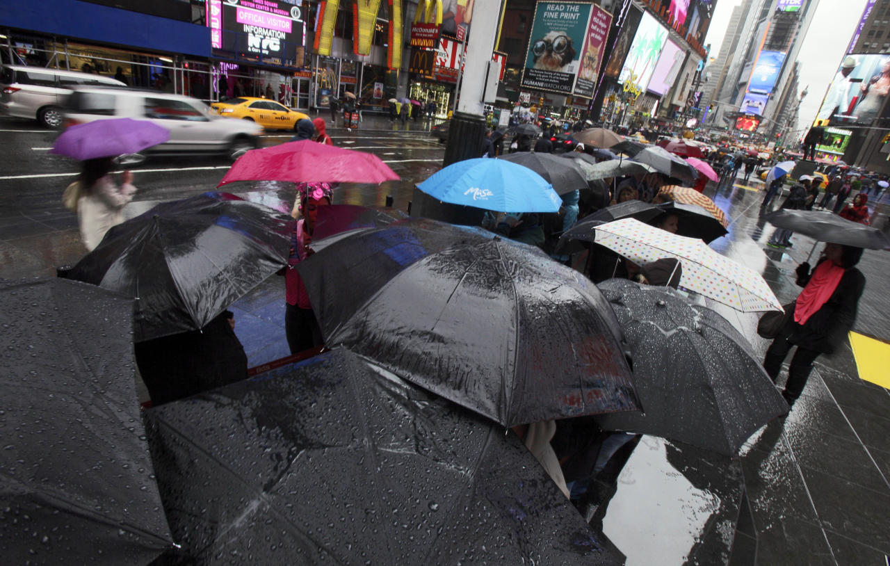 Umbrellas shelter people waiting to buy Broadway theater tickets in New York's Times Square, Sunday, April 22, 2012. A spring nor'easter rumbled along the East Coast on Sunday and was expected to bring rain and heavy winds and even snow in some places as it strengthens into early Monday, a punctuation to a relatively dry stretch of weather for the Northeast. (AP Photo/Richard Drew)