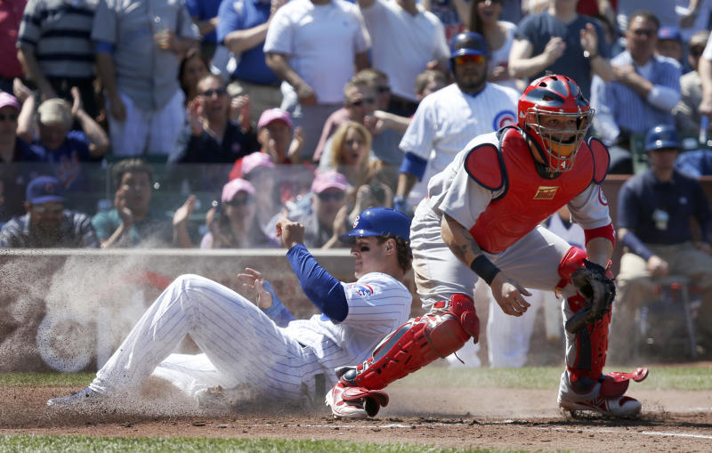 Chicago Cubs' Anthony Rizzo, left, scores past St. Louis Cardinals catcher Yadier Molina on an RBI double by Nate Schierholtz in the fourth inning of a baseball game, Wednesday, May 8 2013, in Chicago. (AP Photo/Charles Rex Arbogast)