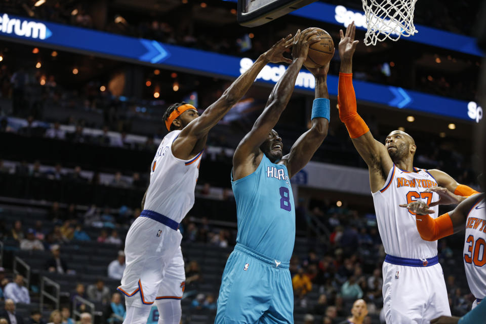 Charlotte Hornets center Bismack Biyombo, center, goes up for a dunk between New York Knicks forward Maurice Harkless, left, and center Taj Gibson during the first half of an NBA basketball game in Charlotte, N.C., Wednesday, Feb. 26, 2020. (AP Photo/Nell Redmond)