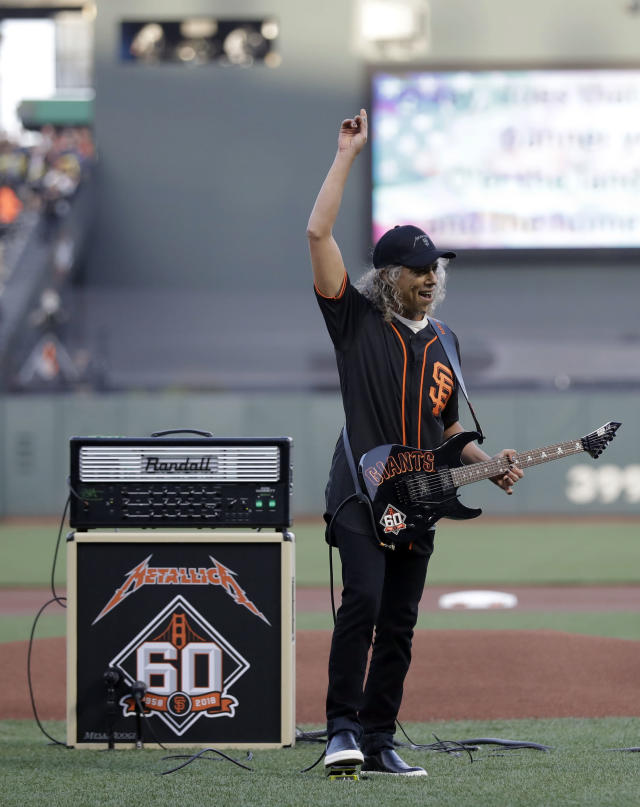 Metallica's Kirk Hammett salutes the crowd after playing the national anthem before throwing the ceremonial first pitch before a baseball game between the San Francisco Giants and the Washington Nationals Monday, April 23, 2018, in San Francisco. (AP Photo/Marcio Jose Sanchez)