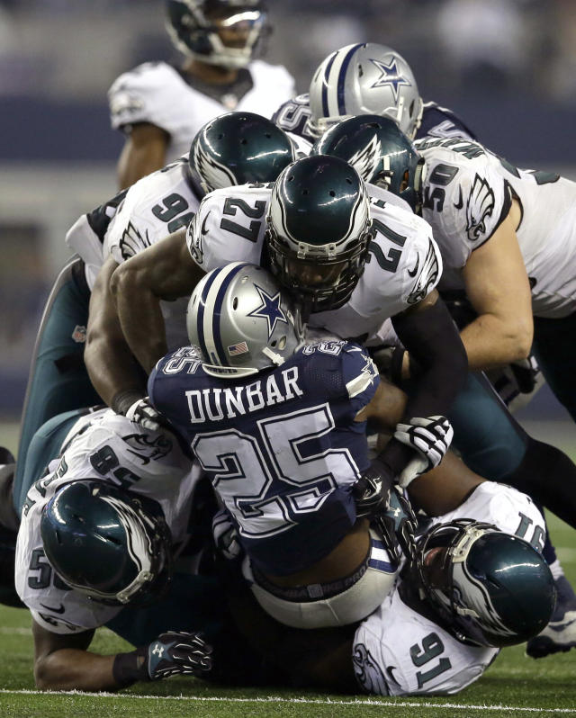 Dallas Cowboys running back Lance Dunbar (25) is stopped on a run by Philadelphia Eagles' Fletcher Cox (91), Trent Cole (58), Malcolm Jenkins (27) and Casey Matthews (50) during the second half of an NFL football game, Thursday, Nov. 27, 2014, in Arlington, Texas. (AP Photo/Tim Sharp)