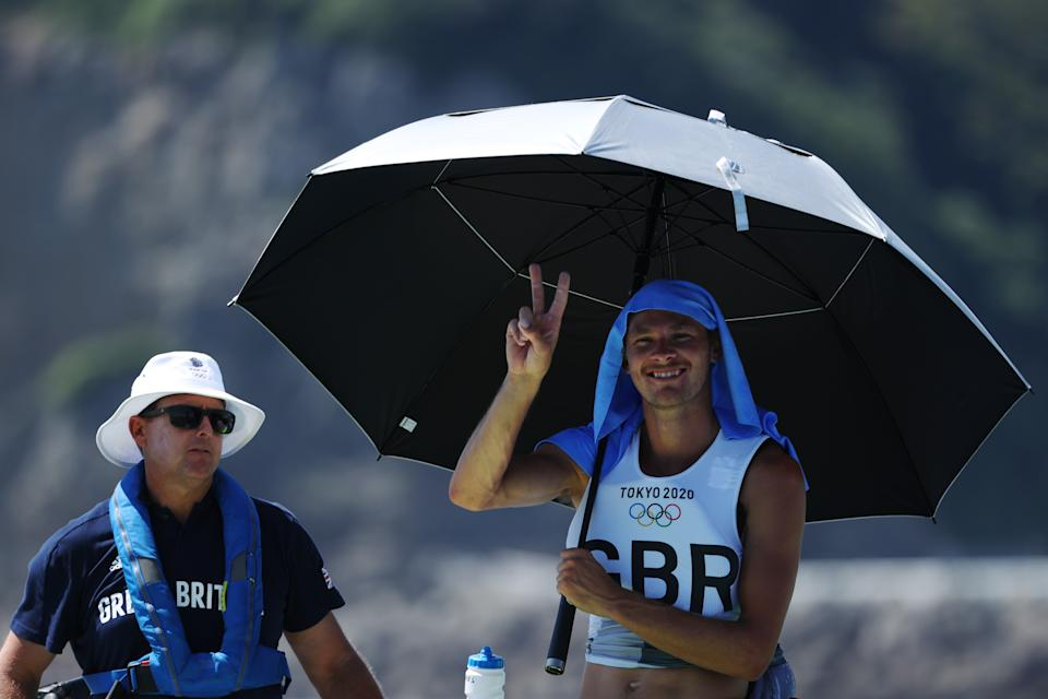 <p>Tom Squires of Team Great Britain shelters from the sun during a competition delay in the Men's RS:X class race on day two of the Tokyo 2020 Olympic Games at Enoshima Yacht Harbour on July 25, 2021 in Fujisawa, Kanagawa, Japan. (Photo by Clive Mason/Getty Images)</p>