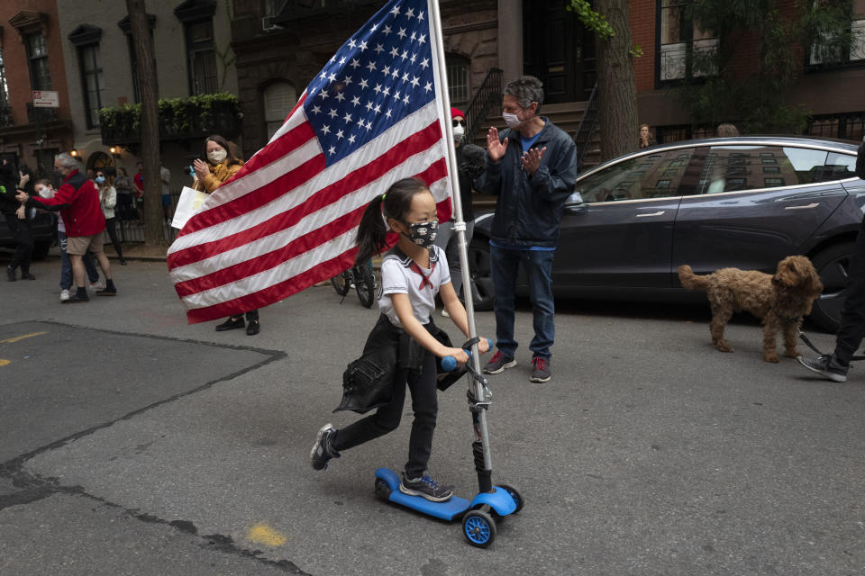 Ai Feng, 6, parades up and down her block with a United States flag in the Greenwich Village neighborhood of New York Thursday, May 14, 2020, during the coronavirus pandemic. The New York City immortalized in song and scene has been swapped out for the last few months with the virus version. In all the unknowing of what the future holds, there's faith in that other quintessential facet of New York City: that the city will adapt. (AP Photo/Mark Lennihan)