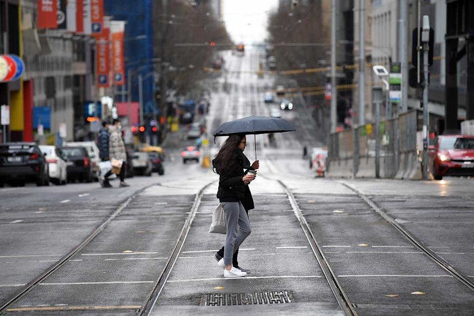 People wearing face masks are seen crossing a road in Melbourne during the state's fifth lockdown during the pandemic. Source: AAP