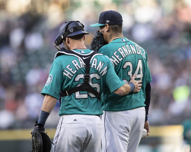 Seattle Mariners catcher Chris Herrmann, left, and starting pitcher Felix Hernandez meet at the pitcher's mound during a baseball game against the Colorado Rockies, Friday, July 6, 2018, in Seattle. The Mariners won 7-1. (AP Photo/Stephen Brashear)